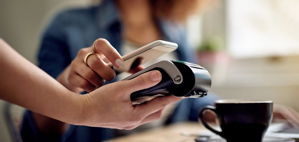 woman paying using NFC technology in a cafe